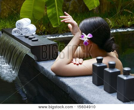 Young woman getting spa treatment at tropical resort