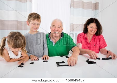 Happy Family Having Fun Playing Domino Game With Kids