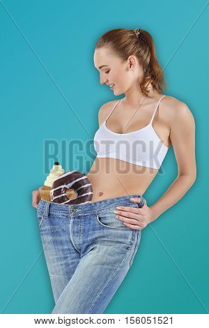 Woman became skinny and wearing old jeans on pink. Concept of healthy lifestyle and beauty