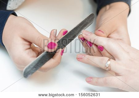 woman in a beauty salon receiving a manicure by a beautician with nail file. manicure closeup