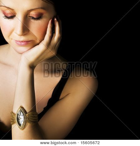 Woman with golden wristwatch on black. Space for text.
