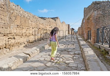 The lonely streets with ruined villas in ancient excavated town of Pompeii nowadays the large archaeological site Italy.