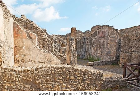 The ruins of the stone housing with preserved plaster wall details Pompeii Italy.