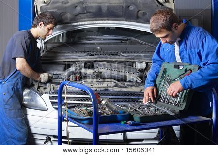 Two auto mechanics working at auto repair shop