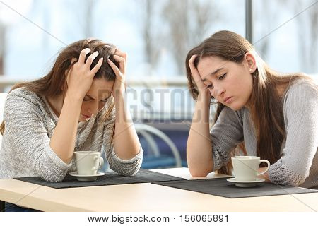 Two sad women worried in a coffee shop with a window in the background