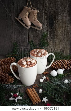 Two cups of hot cocoa or hot chocolate with christmas tree branches, old fashioned skates, cinnamon sticks,anise stars and cozy. Traditional christmas beverage.Winter still life.