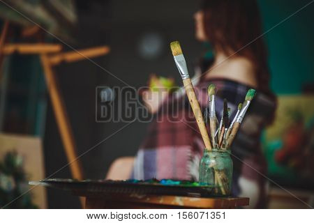 Closeup Of Painting Brushes Against The Background Of A Woman Artist