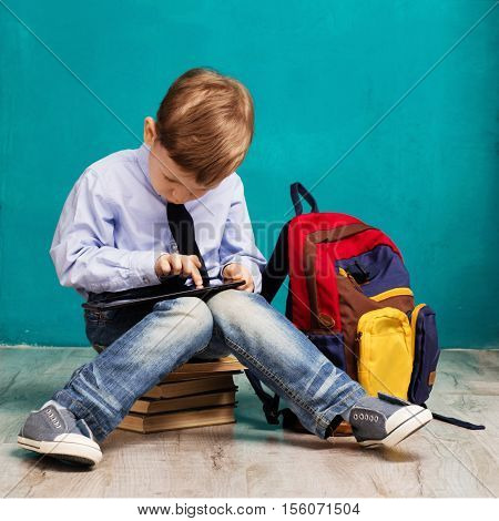 Cheerful Little Boy With Big Backpack Holding Digital Tablet Against Blue Background