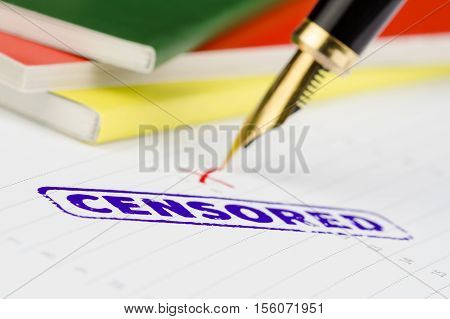 Censored stamped on a paper colorful books and pen.
