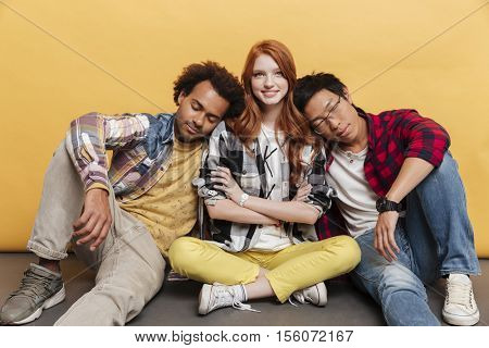 Two tired young men sitting and sleeping on shoulders of smiling girl over yellow background