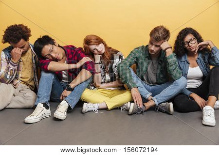 Multiethnic group of exhausted young friends sitting and sleeping over yellow background