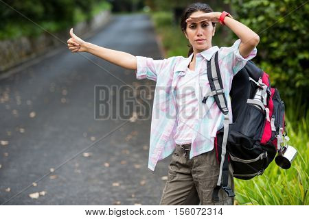 Woman hitchhiking on countryside road in forest