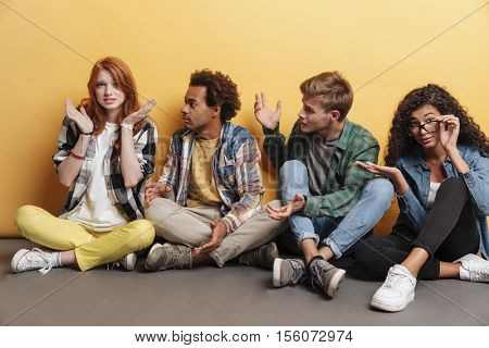 Multiethnic group of friends sitting and blaming unsure embarrassed girl over yellow background
