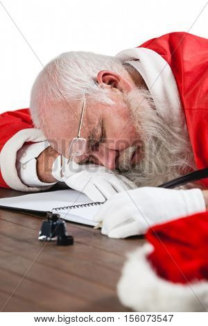 Santa claus sleeping at desk while writing a letter with a quill during christmas time