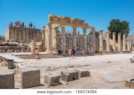 LINDOS RHODES ISLAND GREECE - JULY 9 2015: Tourists visiting in the Acropolis of Lindos. In the center Staircase of the Propylaea