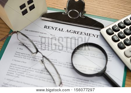 rental agreement contact with an architectural model and a calculator and glasses and magnifier