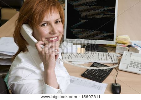 Woman at her work place. Portrait of programmer.