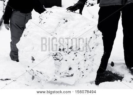 Black and white image of a child rolling a large snowball in the snow to make a snowman