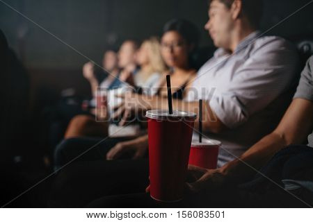 Close up of people with soft drinks in movie theater focus on cold drink glass.