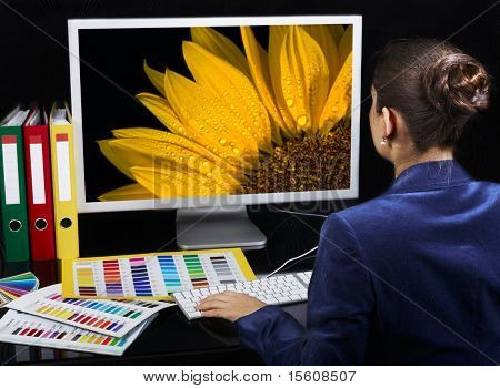 Designer at work. Vivid photo on computer monitor.