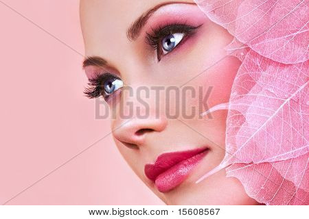Beautiful woman face with pink makeup and leaves