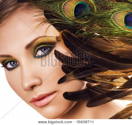 Woman face with beautiful makeup and feathers