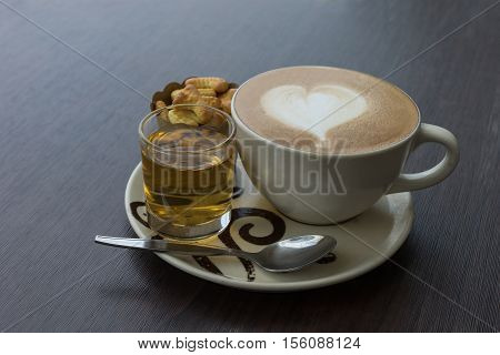 hot fresh coffee in white glass hot tea and alphabet biscuit with tree shape of heart foam on wooden table city view at sunset at coffee time / hot fresh coffee and tea