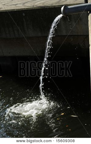 water coming out of a pipe and flowing into a river