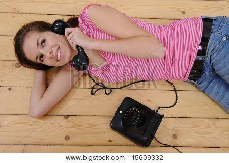 beautiful girl lying on the floor and talking on phone at home
