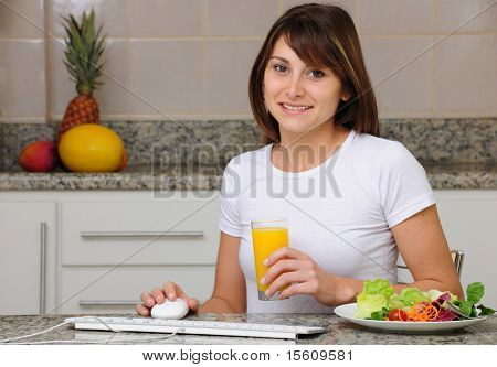 woman eating a salad and working on computer at home