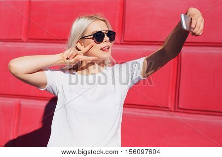Close-up of trendy teenage girl in sunglasses is making selfie photo over a red wall, showing peace sign and grimacing