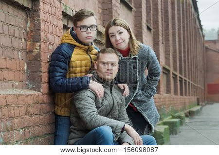 Family of three street urban portrait at red brick building wall background