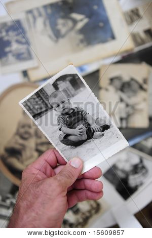remembering childhood:  man holding photo of himself as a boy