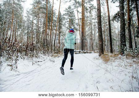 young woman runner running a winter marathon on a snowy park