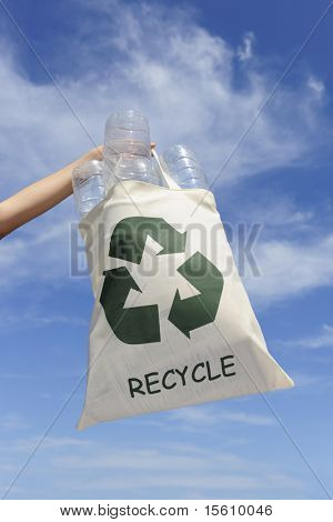 recycling: hand holding bag with plastic bottles against blue sky