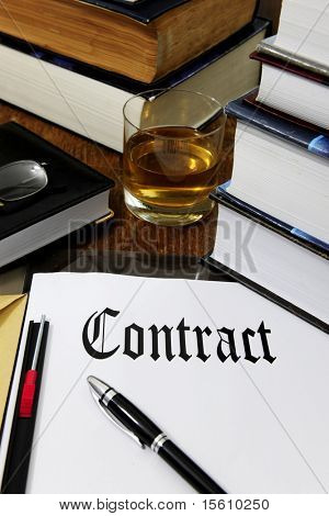 contract, whiskey, pen, books on a desk