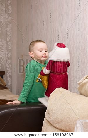 the little boy talks to a figure of Santa Claus waiting for Christmas