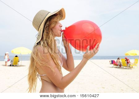 party prewoman inflating a red balloon on the beach
