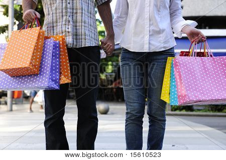 summer sale: couple with shopping bags crossing the street