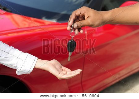 car dealership: woman receiving car key from salesman