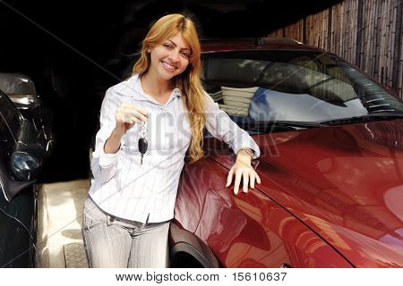 happy woman showing key of new red sports car