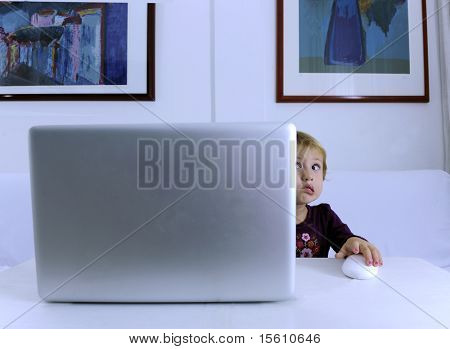 nerd child alone scared with a virus problem on laptop computer surfing the Internet