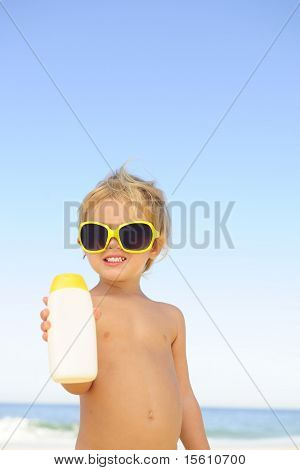 child with sunglasses showing sunblock at the beach
