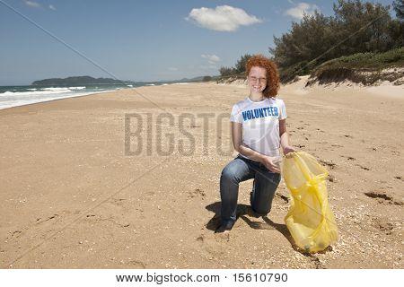 Jovem feminino voluntário coletando lixo na praia