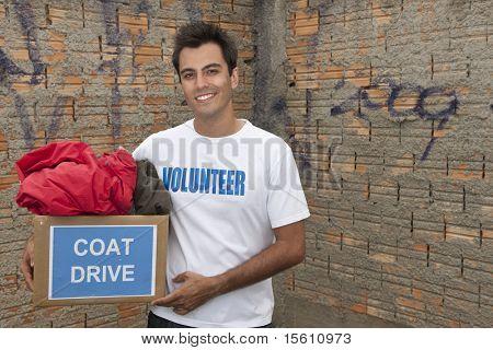 happy hispanic volunteer with coat drive donation box