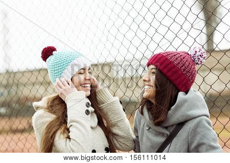Two cheerful teenage girls laughing, enjoying outdoors on cold day, wearing colorful knitted beanie hats and coat. Spontaneous, unposed, no retouch, natural light