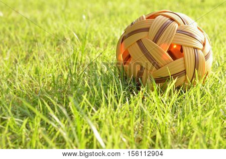 Rattan ball on green grass in evening day,sport equipment.