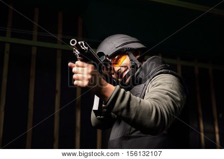 Man with a gun wearing a bulletproof vest and helmet