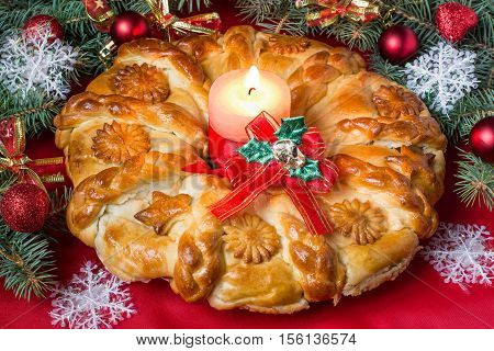 Creative homemade cake of yeast dough filled with cheese. The original festive cake in the form of a Christmas wreath on the background of branch Christmas tree with decoration Creative homemade cake of yeast dough filled with cheese. The original festive
