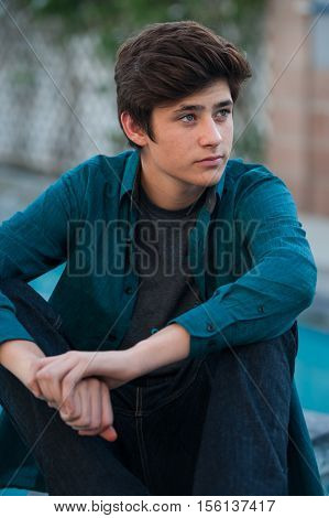 Handsome Latino teen seated while looking off to right.